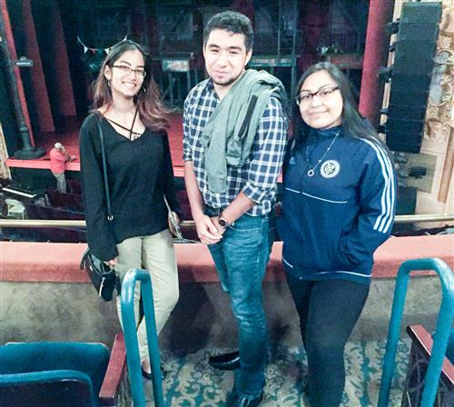 three students in a broadway theater